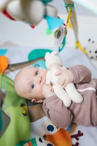 photo of a baby holding and sucking on a toy