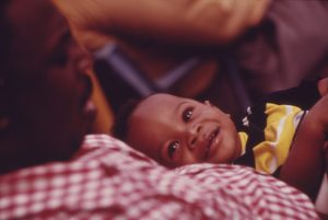 a toddler boy smiles looking up at his father sitting with him