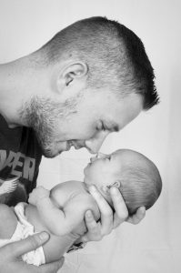 a man holding an infant close to his face and smiling
