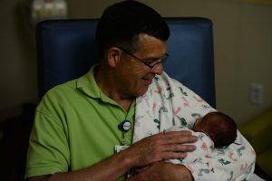 A man sitting holding a newborn infant