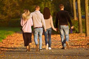 Two young adult couples walk together with one couple holding hands and the other with arms around each other