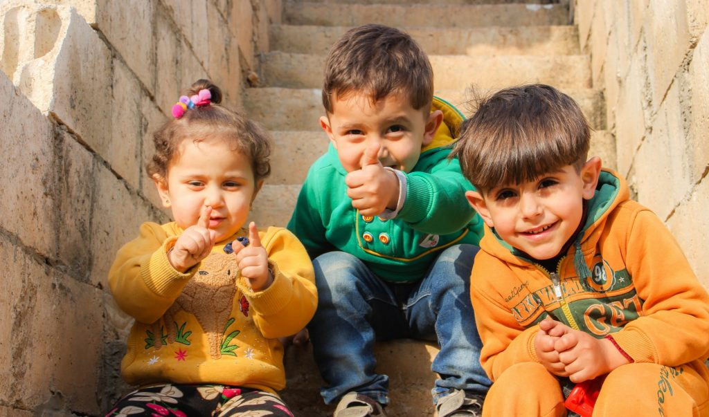 Young children smiling and gesturing