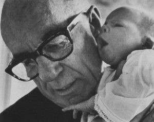 A black and white photo of Dr Spock, an old man, holding a baby.
