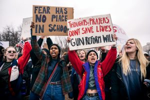 A photo of young adults holding signs protesting for gun laws at the White House