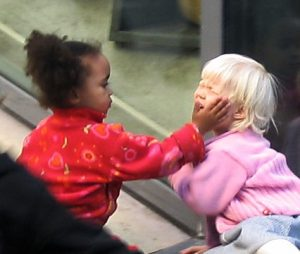 photo of child with her hand on another childs face