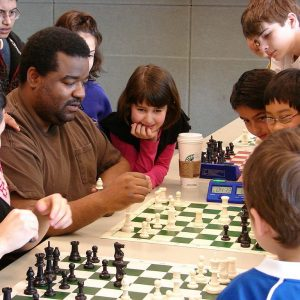 A group of children watch as adults play a game of chess.