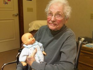 An elderly woman is holding a baby doll.