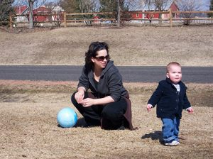 A person sitting near a small child who is standing up and looking around.
