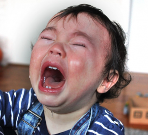 A red-faced toddler screams with tears streaming down their face.