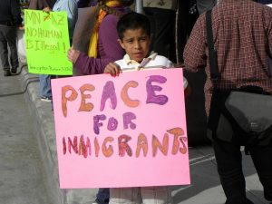 """A young boy in Minneapolis holds a a poster that reads """"Peace for Immigrants"""""""