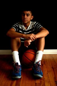 a photo of a boy sitting on the ground with a basketball