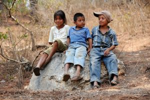 photo of three children sitting on a large rock outside