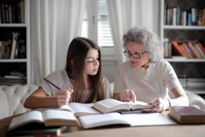Photo of an older woman and girl sitting at a table. The older woman is helping to teach the girl who is studying.