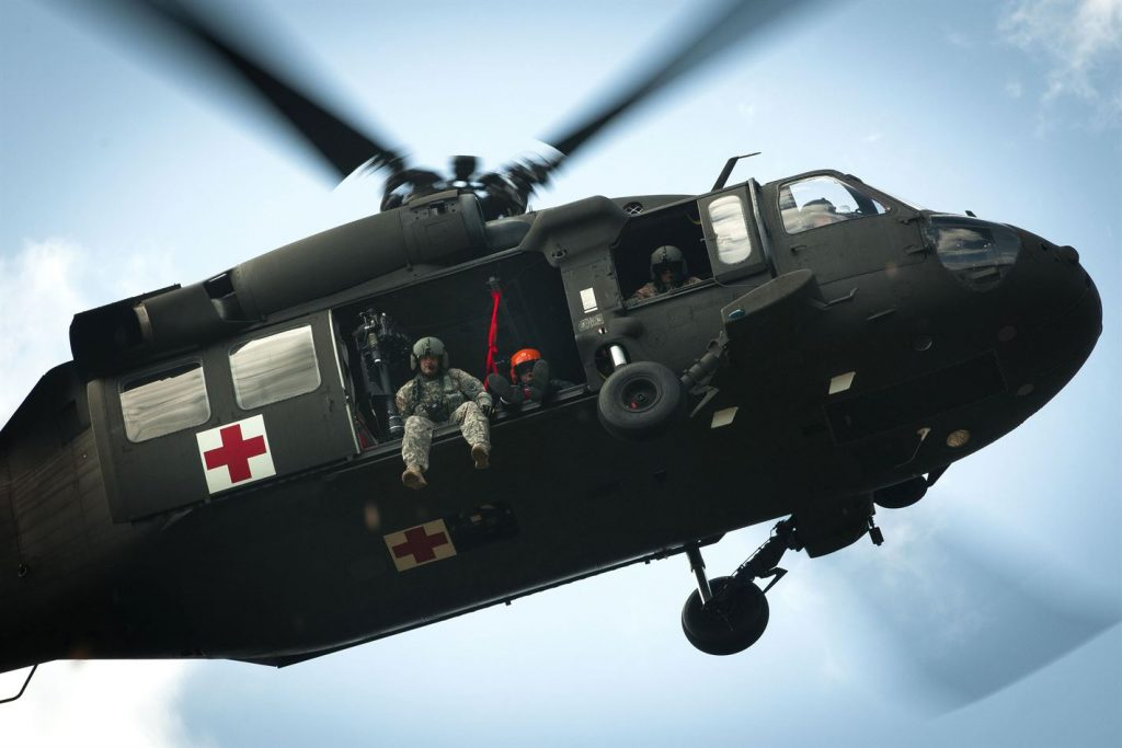 an army helicopter hovers overhead, with soldiers looking down at the camera