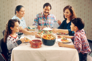 photo of a family sitting at the table eating dinner together