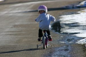 a young girl riding a bike with her head turned looking behind her