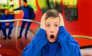 a boy with his hands on his face and mouth opened in a shocked expression
