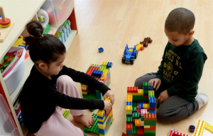 two children play with Legos together on the floor