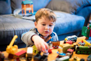 a young boy plays with train toys at a table