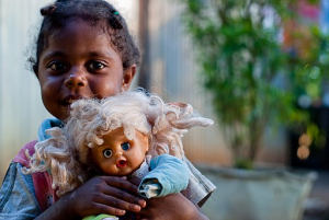 a young girl holding a doll