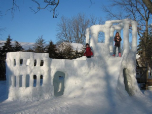 photo of a large snow fort with two children on it