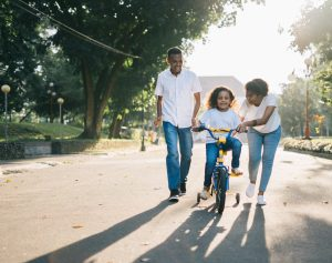 A father and mother walk alongside their daughter who is learning to ride a bike