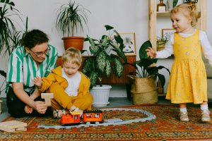 Photo of a mother with her toddler son and daughter playing with trains