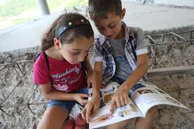 a young boy and a young girl sit next to each other reading a book together