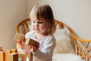 Photo of a young child playing with wooden blocks