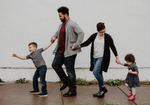 Photo of a father, mother, son and daughter walking together on a sidewalk